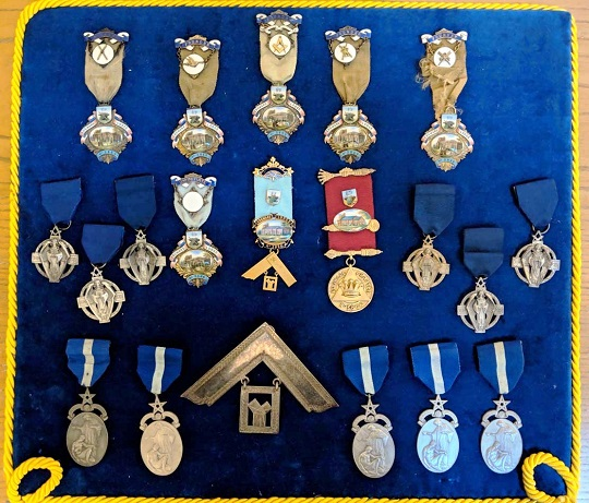 <center>Display of Lodge Jewels -  Top Row. 4 Founders Jewels flank the central jewel which was <br>the Consecrating Officers Jewel <br>           2nd row - 6 Masonic Million Memorial medals flank a PM Jewel in the centre with the 2nd Initiates <br>Jewel to its left and a PZ Jewel to the right. <br>3rd row - centrally is a PM Collar Jewel engraved to several Members of the Lodge surrounded by<br> Lodge Members Hospital Jewels.</center>