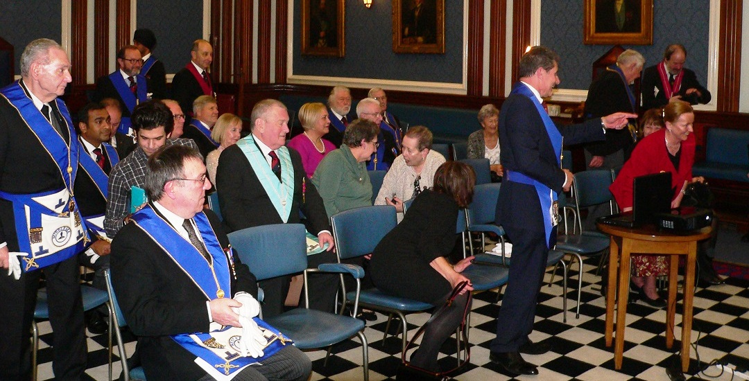 Freemasons in regalia and ladies sitting in the Temple waiting for the talk to commence