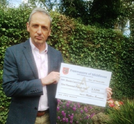 Maurice Austin, Trustee and Treasurer of HANDS, displaying the <br>cheque